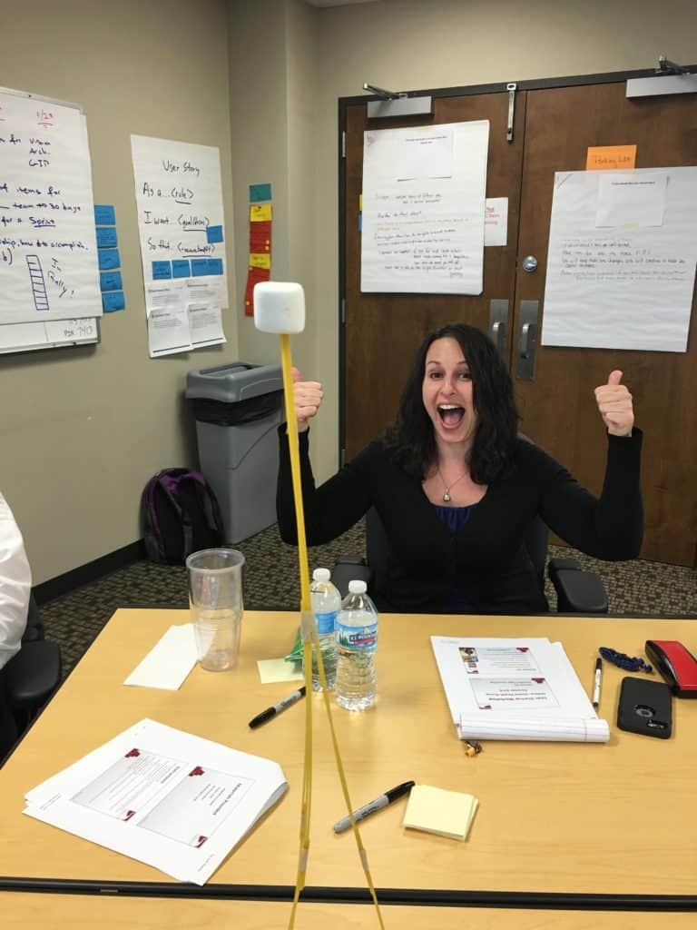 Work, me at work, girl with two thumbs up excited to win a competition with the tallest structure made from pasta, a marshmallow, and a rubber band